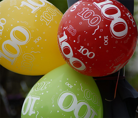 A red, yellow and green balloons with 100 written all over them.