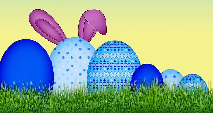 Blue decorated eggs on a bed of grass with bunny ears behind the largest egg.