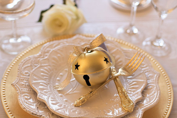 Off white dishes with gold bells and sliverware.