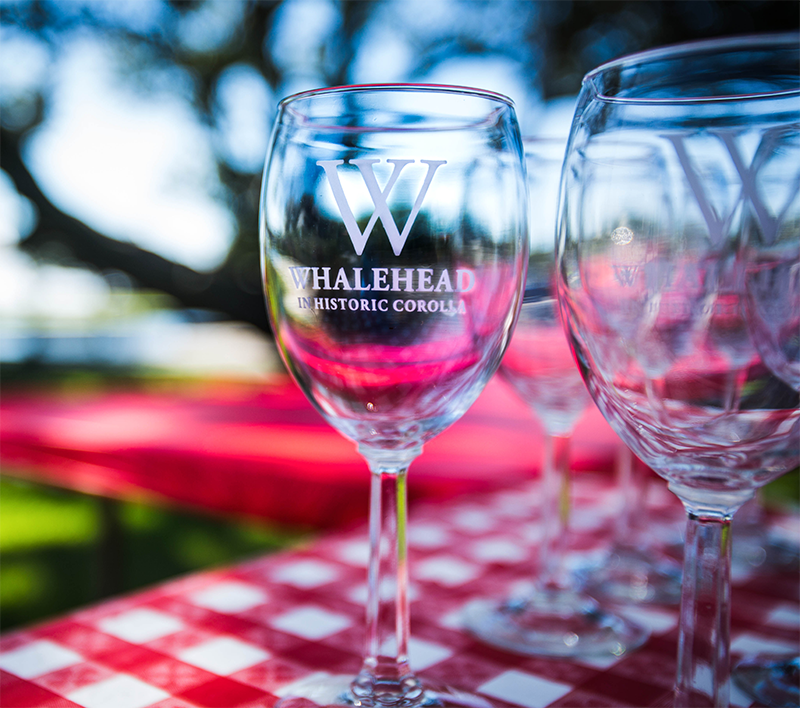 Whalehead in Historic Corolla wine glasses with a blurred background.