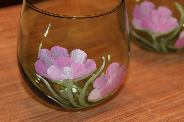 Glass with pink flowers painted on it.