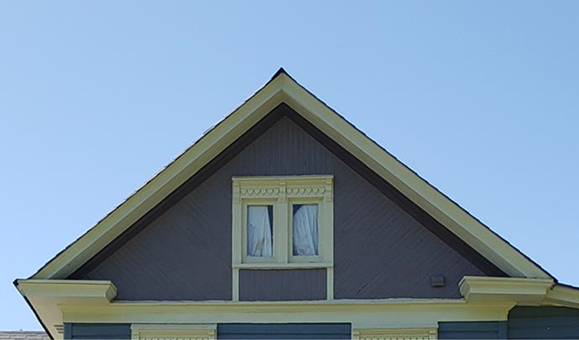 Close up of gable end, molded cornice, sunburst pattern, paired single light windows with molded drip edge and sawtooth ornament.