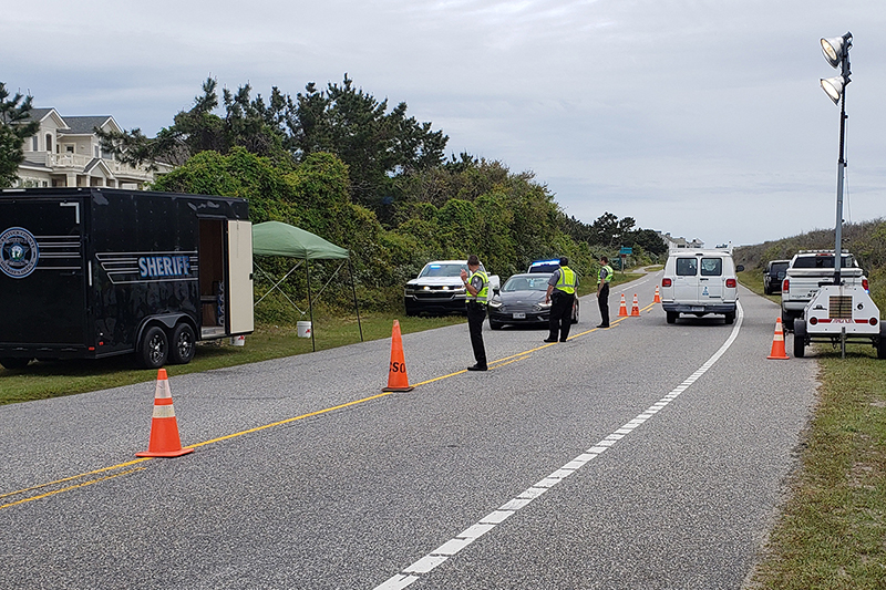 Re-entry checkpoint in Corolla. Several Sheriff Deputies with cars and the Sheriff's trailer.