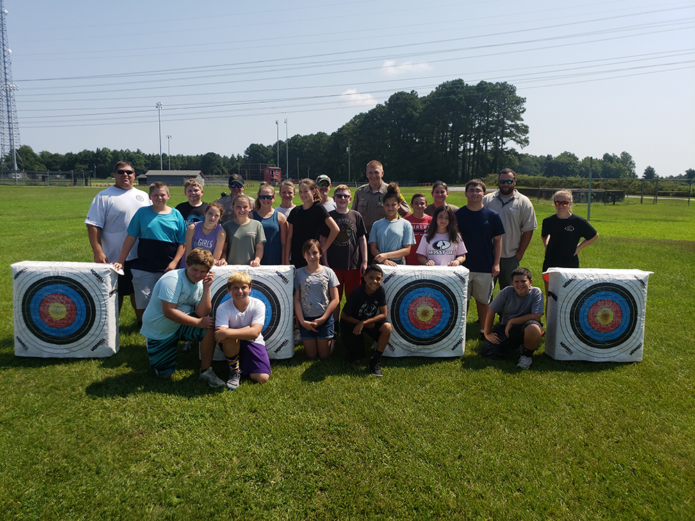 Teens and staff standing behind archery targets.