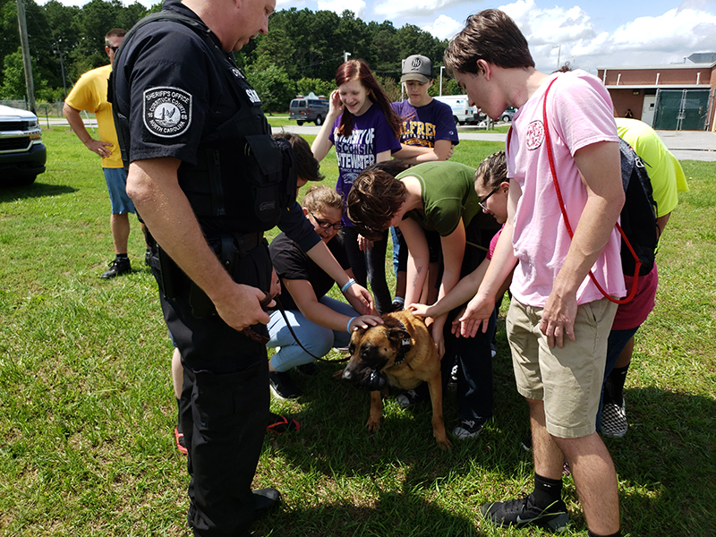 Teens petting the one of the K-9 dogs with his handler.