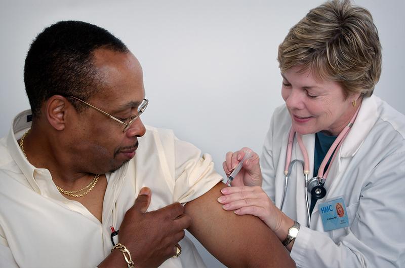 Man getting his flu shot from a nurse.