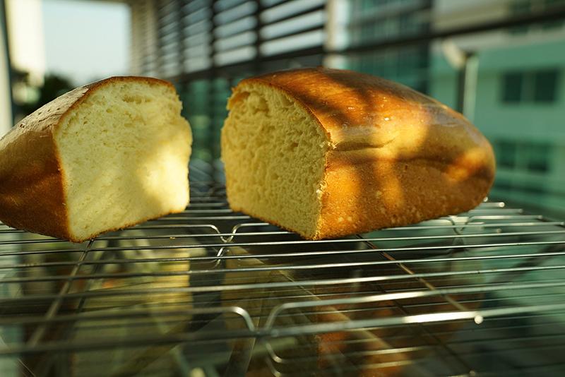 Loaf of bread sliced in half on a cooling rack.