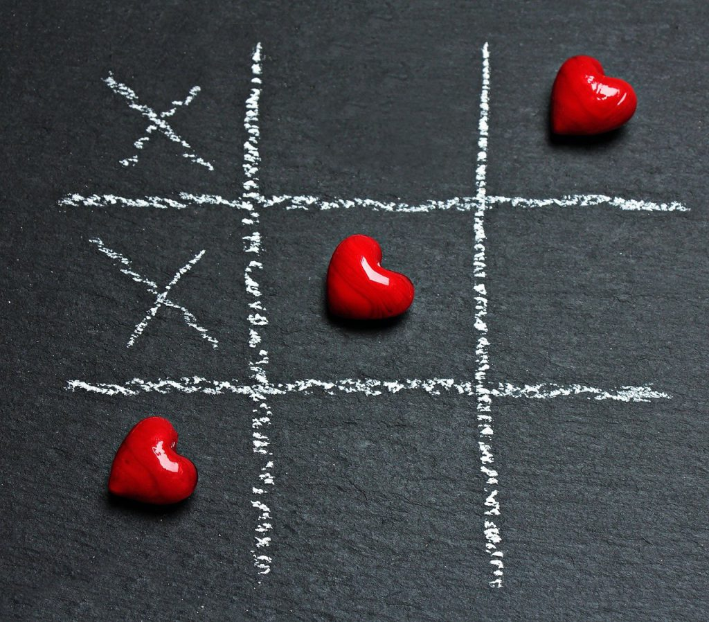 Tic-Tac-Toe game on a black background with 3 red hearts in a row.
