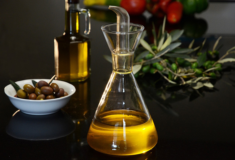 Decorative Oil decanter, bowl of olives and bottle of oil.