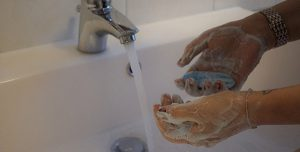 Washing hands in a sink with soap and water